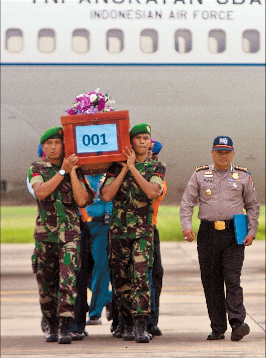 Indonesian military personnel carry the coffin of a victim recovered from the ill-fated AirAsia flight QZ8501, upon arrival at the military airbase in Surabaya, East Java, yesterday. [Photo/Shanghai Daily]
