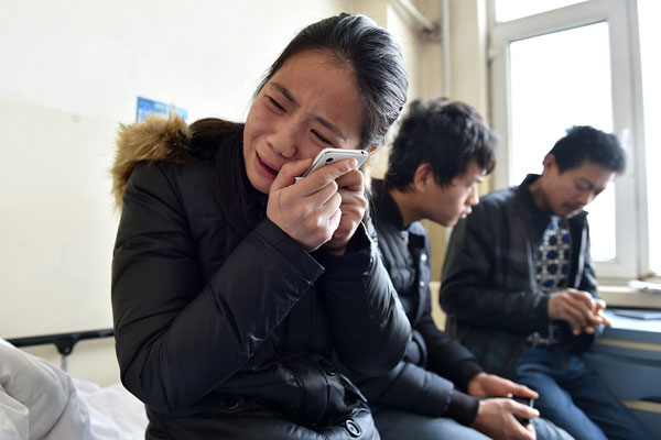 Wang Qian, daughter of Zhou Xiuyun, a 47-year-old female worker who was beaten to death, cries while looking at a photo of her mother. Zhou was one of the 10 migrant workers who were trying to enter a construction site in Taiyuan on Dec 13 to demand their salaries and argued with guards. [Photo / Xinhua]