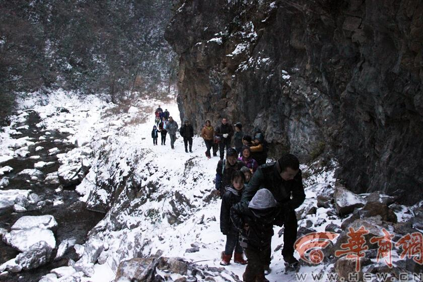 Elementary students and their parents walk on a snow-covered mountain road to school in Guanyin township, Zhenba county, Northwest China's Shaanxi province, Jan 29, 2015.[Photo/HSW.cn]
