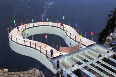 Workers stand on the cantilever bridge at Longgang scenic area in Yunyang, southwest China's Chongqing municipality.[Photo/Xinhua]