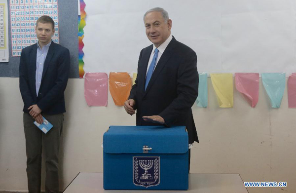 Israeli Prime Minister Benjamin Netanyahu (R) casts his ballot at a polling station during the parliamentary election in Jerusalem, on March 17, 2015. Israel held parliamentary election on Tuesday.