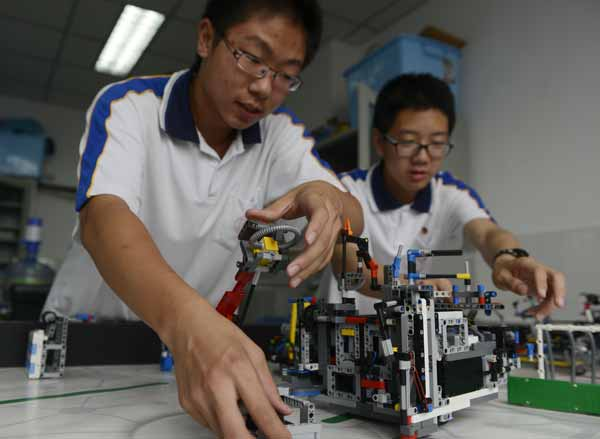 Guo Zhuoxuan (left) and Zhang Xinyu, members of a robotics club at the middle and high school affiliated with Jiaotong University in Beijing, calibrate their robot on Thursday. [Photo/China Daily]