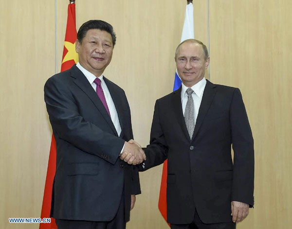 Chinese President Xi Jinping (L) shakes hands with his Russian counterpart Vladimir Putin in Ufa, Russia, July 8, 2015. [Xinhua]