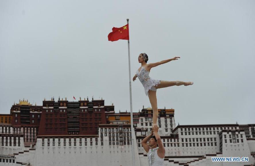 Acrobats Wei Baohua and Wu Zhengdan perform at the Potala Palace Square in Lhasa, southwest China's Tibet Autonomous Region, Aug. 3, 2015. Artists from Xinlianxin Art Troupe, organized by China's Central Television, started a tour in Tibet on Monday to mark the 50th anniversary of the establishment of Tibet Autonomous Region. [Photo: Xinhua]