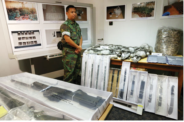 A police officer displays weapons and other contraband goods during a news conference on operation 'Thunderbolt 15' on Wednesday. [Photo by Roy Liu / China Daily]