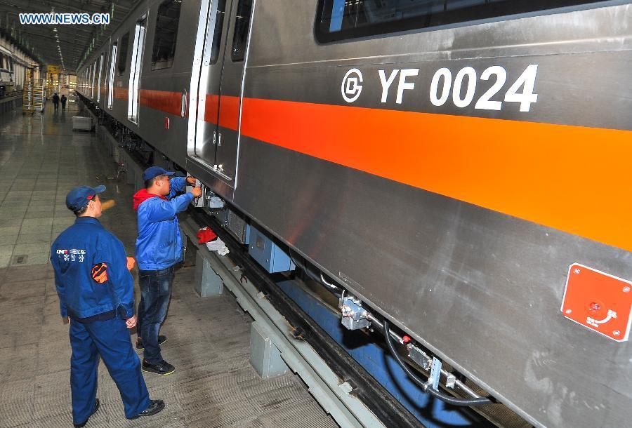 10月15日,中车长客员工在对北京燕房线地铁列车进行收尾作业。近日,我国国内首列全自主化、全自动驾驶的北京燕房线地铁列车在中国中车长客股份公司下线,预计将于11月底进行首列列车的交付工作。据介绍,北京燕房线地铁列车采用4辆编组,车辆最高运行时速80千米,是我国自主开发的自动化等级最高的地铁列车,可实现自动唤醒、自检、自动运行、上下坡行驶、到站精准停车、自动开闭车门、故障情况下自动恢复等全套操作。 [新华社] Workers tie up loose end of the autopilot subway