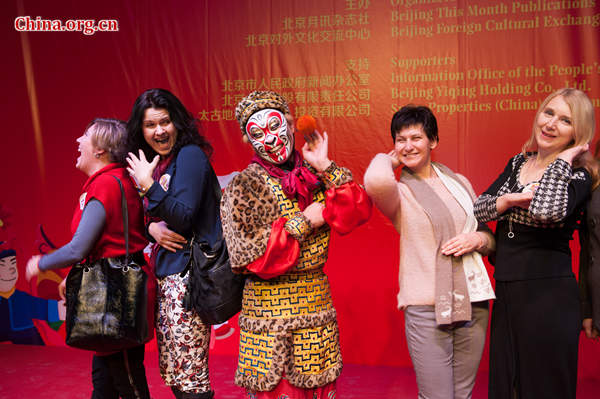 Foreigners learn to make a monkey face from a Peking Opera artist at the 'Beijing Salon – Experience Beijing'on Wednesday. [Photo by Chen Boyuan / China.org.cn]