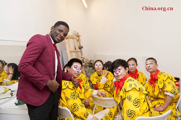 Nathan Diwambuena Miayiza, a DR Congolese student studying in Beijing poses for photos with a group of Peking Opera performers at the 'Beijing Salon – Experience Beijing' on Wednesday. [Photo by Chen Boyuan / China.org.cn]