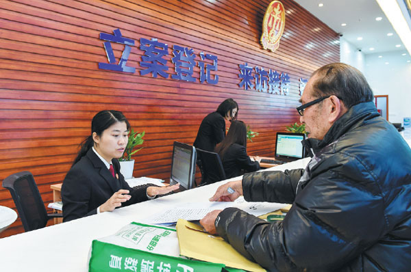 A man applies to file a case with a clerk at the First Circuit Court of the Supreme People's Court in Shenzhen, Guangdong province, on Feb 2, 2015. [Photo/Xinhua]