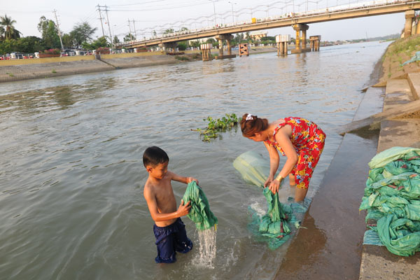 A woman and her son wash bags in the Mekong River on Monday. Photos by Xinhua, Wang Jian / China Daily and provided to China Daily