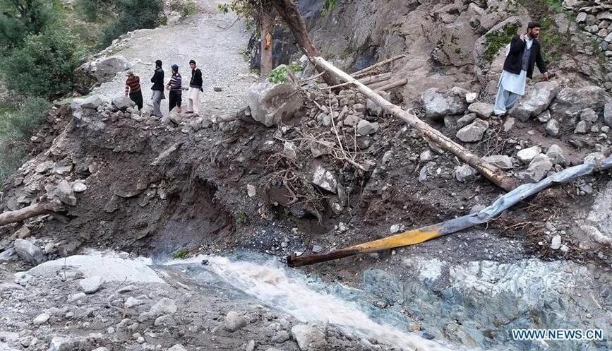 Pakistani people stand on a road destroyed by landslide in northwest Pakistan's Kohistan on April 6, 2016.[Photo/Xinhua]