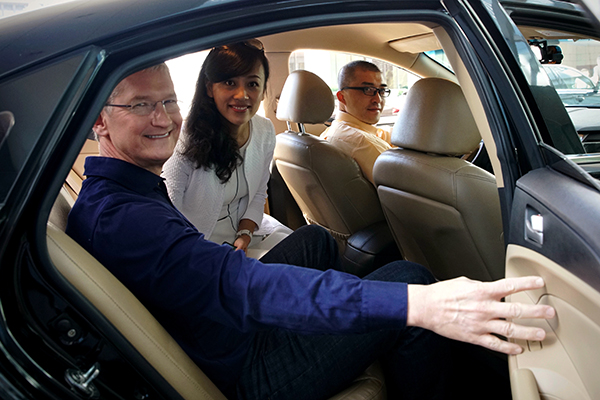 Apple CEO Tim Cook takes a taxi hailed via Didi with Jean Liu Qing, president of Didi, to an Apple store in Wangfujing in downtown Beijing on May 16, 2016. Cook's visit follows Apple's investment of $1 billion in the Chinese ride-hailing service. [Provided to chinadaily.com.cn]