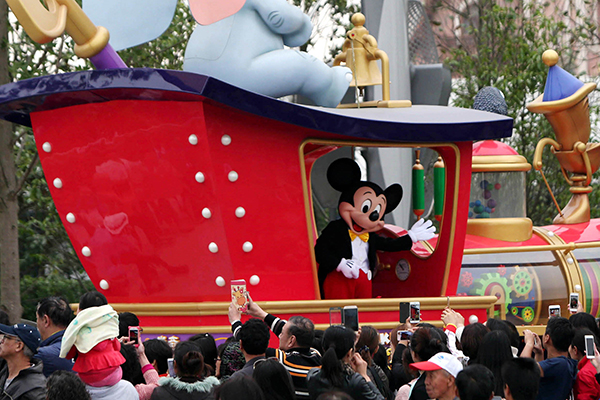 Visitors take photos during a parade at the Shanghai Disneyland park. [Photo/Xinhua]