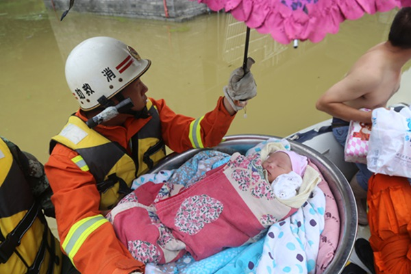 A rescuer escorts a sleeping 10-month-old infant to safety on Tuesday in Xiaba, a village in Guizhou province that has been left submerged by consecutive heavy downpours. [Photo/China Daily]