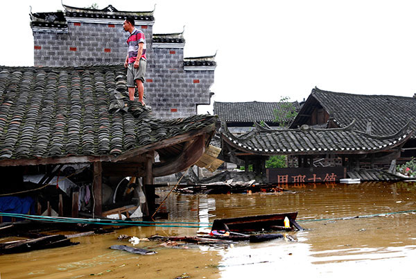 A man stands on the roof of his home, which is steeped in water in the ancient town of Liye in Longshan county, Hunan province, on Tuesday. [Photo/China Daily]