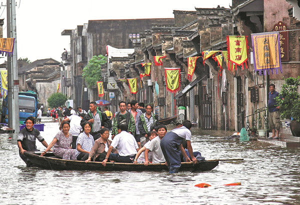Residents are moved to safety on Sunday in Tongling, Anhui province, as flooding continued to affect the city and other regions in central and eastern China. [Photo by Zhan Jun/For China Daily]