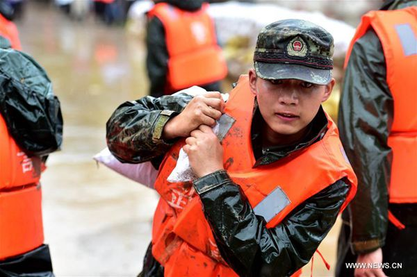 A soldier carries a sandbag to reinforce the Dadao dyke of Baidang Lake in Tanggou Township of Zongyang County, east China's Anhui Province, July 6, 2016. Over 260 soldiers were dispatched to reinforce the dyke. [Photo/Xinhua]