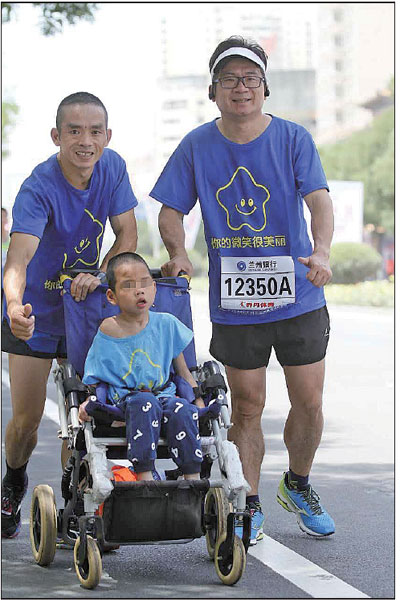 Luo Shujian (left) runs with his son Xiao Bo at a marathon event held in Lanzhou, Gansu province. [Photo/China Daily]