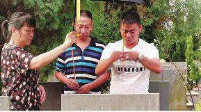 Ma Jianhua (right) and Li Rongfu (middle) pay respect to their deceased parents after going home 44 years later. [Photo/Huashang Daily]