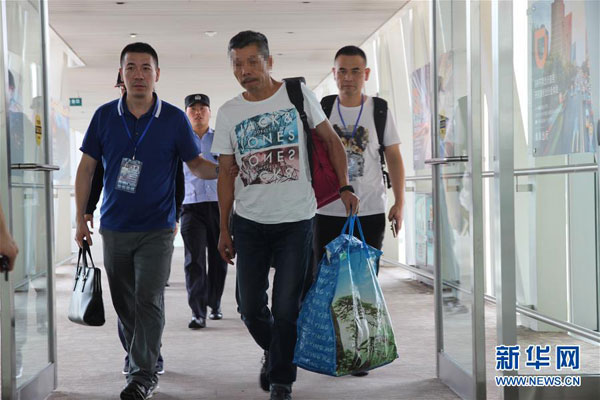 A fugitive repatriated from France arrives in Beijing on September 15, 2016. [Photo: Xinhua]