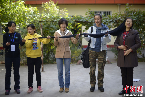 File photo of Ni Linmei (R) demonstrating her hair, which was then 2.9 meters in length, with the help of her friends in October,2013.(Photo: China News Service)