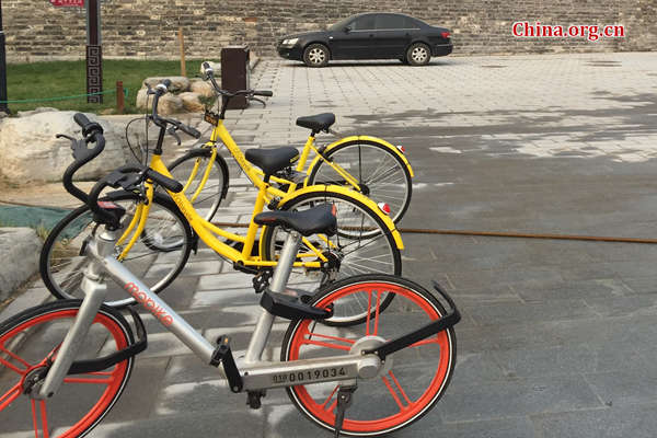 A Mobike is parked next to two Ofo bikes. [Photo by Guo Yiming / China.org.cn]
