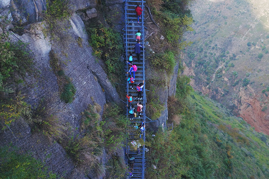 Children climb a steel ladder leading to the cliff village in Sichuan province on Saturday, November 19, 2016. [Photo: The Beijing News]