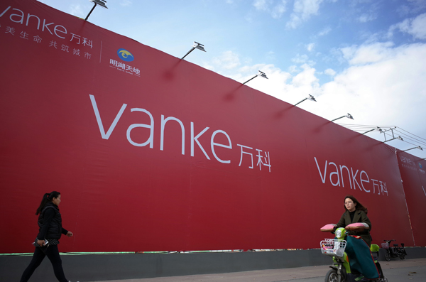 Pedestrians walk past an advertisement board of China Vanke Co Ltd. [China Daily]