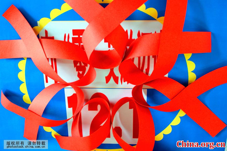 """剪制和展示预防艾滋病徽标""""红丝带"""",宣传""""防艾""""知识,迎接12图片"""