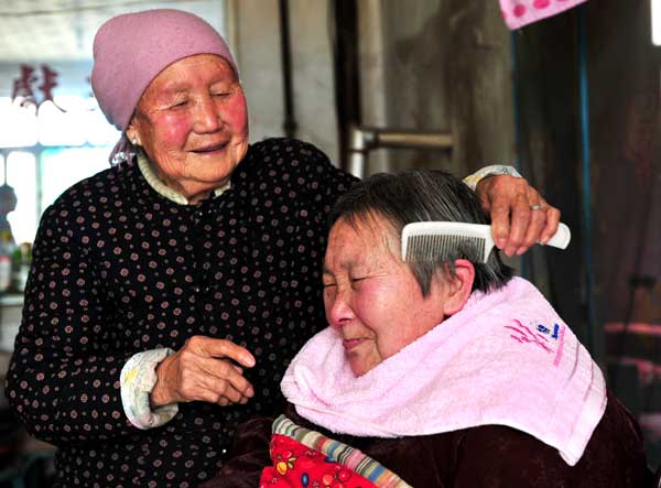 Sun Yincong combs the hair of her daughter-in-law Ren Caimei at their home in Yuncheng, Shanxi province. [For China Daily]