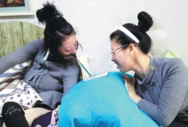 Typing on a tablet computer is hard work for Tian Xiaolu. [Photo/China Daily]