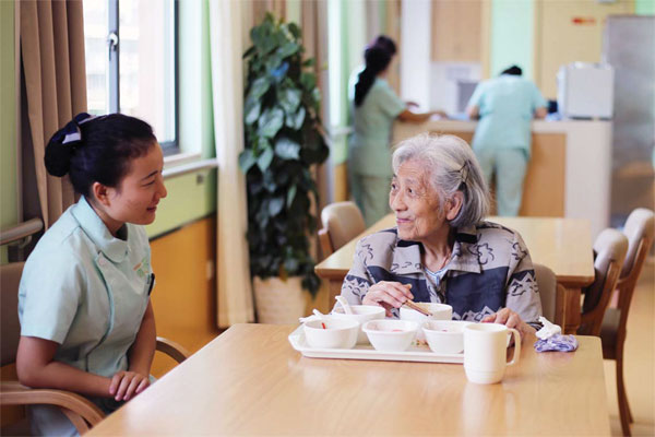 An undated photo shows an elderly woman dining at a nursing home in Hangzhou. [Sun Yidou/For China Daily]