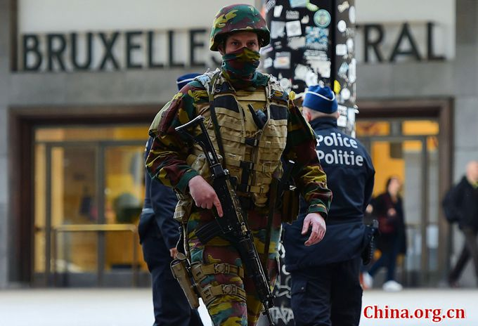 A Belgian soldier patrols outside Brussels Central Station as people are allowed in small group of ten to reach the station in order to take their commuter train following attacks in Brussels on March 22, 2016. [Photo/China.org.cn]