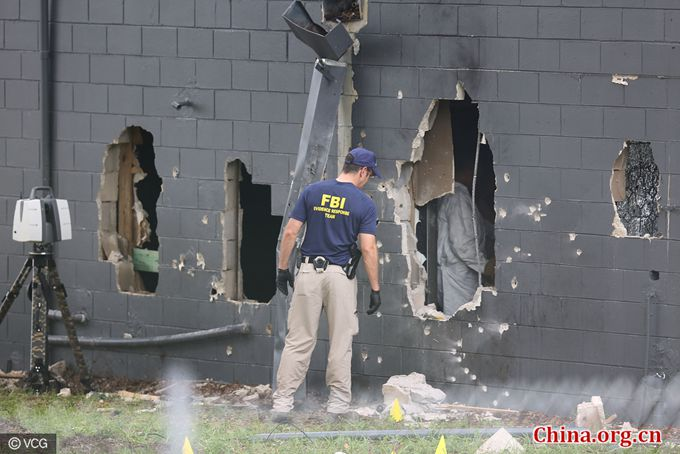 FBI agents investigate the damaged rear wall of the Pulse Nightclub where Omar Mateen allegedly killed at least 50 people on June 12, 2016 in Orlando, Florida. [Photo/China.org.cn]