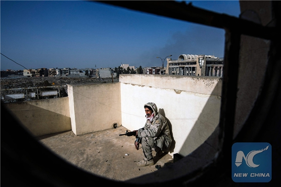 An Iraqi army soldier takes position during a battle against the Islamic State (IS) group near the Fourth Bridge over the Tigris River connecting eastern and western Mosul on January 10, 2017. [Photo/Xinhua]