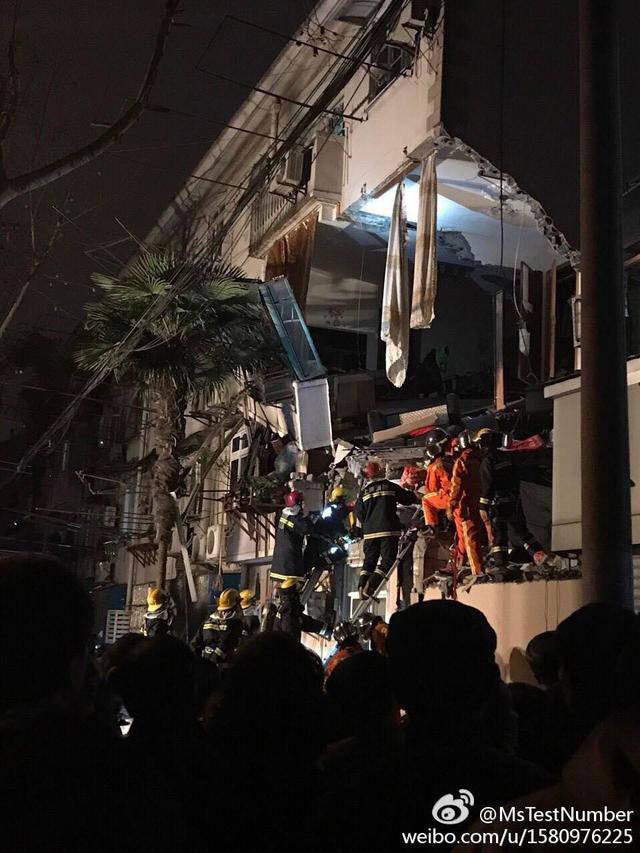 Firefighters try to rescue trapped residents from a residential building in Shanghai, which has been seriously damaged, reportedly by an explosion, on Wednesday, January 11, 2017. [Photo: weibo.com]
