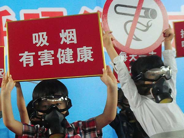 Children wearing gas masks hold anti-smoking signs to call on their parents to quit smoking at an event in Hangzhou on May 29, 2016.Lian Guoqing / For China Daily