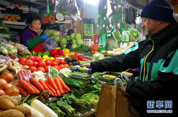 A foreigner buys vegetables in a food market in Beijing's Chaoyang District on Jan. 26, 2017. [Photo/Xinhua]