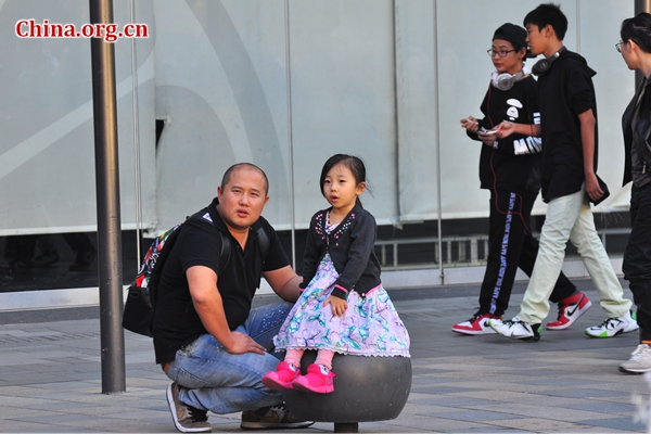A little girl sits on a stone in Sanlitun, Beijing's Eastern Chaoyang District, accompanied by her parent in early spring. [Photo by Guo Yiming / China.org.cn]