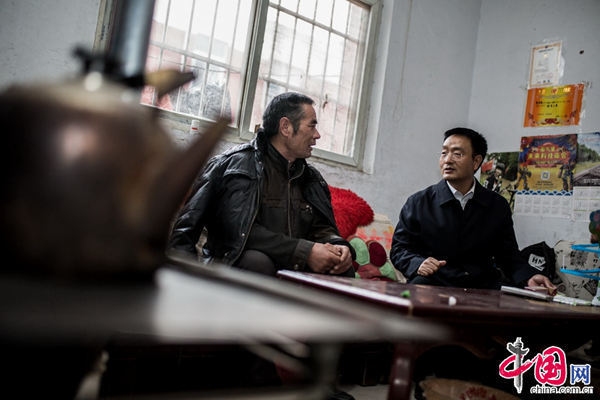 'I keep to my rule of visiting the villagers' homes and sharing meals with them every month,' says Pei (R), explaining that in this way he can access the locals' true feelings and build a deeper bond with them. [Photo by Zheng Liang/China.org.cn]
