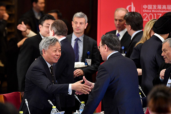 Asian Infrastructure Investment Bank (AIIB) President Jin Liqun (L) speaks with a guest during the China Development Forum (CDF) 2017 in Beijing, March 19, 2017. [Photo/Xinhua]
