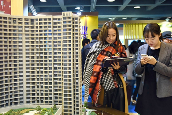 Prospective home buyers check out new property prices at a sales event in Hangzhou, Zhejiang province, East China, on Dec 17, 2016. [Photo/China Daily]