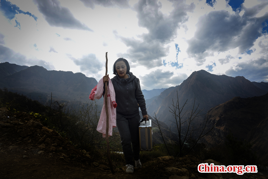 Ma Li is on her way to visit a patient. She has worked as a doctor in a small clinic in Luoju Village, Mianning County, Liangshan Yi Autonomous Prefecture in Sichuan Province, for 16 years. [Photo by Pan Songgang/China.org.cn]