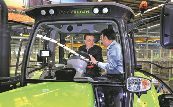 Premier Li Keqiang receives an introduction to the Zoomlion 230-horsepower tractor from the company's deputy director, Wang Jinfu, in Kaifeng, Henan province, on Monday. [Photo/China Daily]