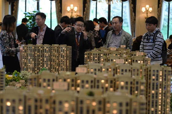 Home buyers examine a property model in Zhuozhou, Hebei province. [Photo/Xinhua]