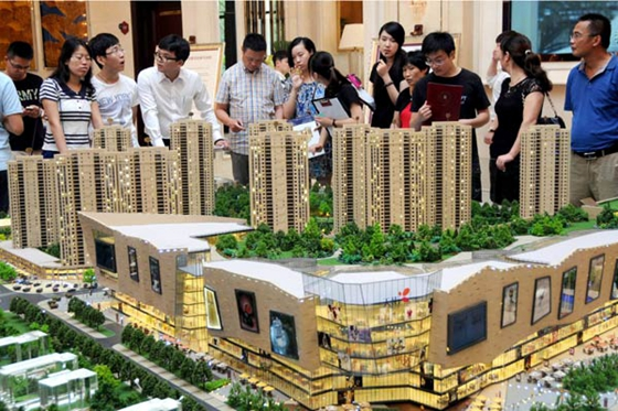Potential homebuyers examine a property project model in Hangzhou, capital of Zhejiang province, Aug 31, 2014. [Photo/Xinhua]