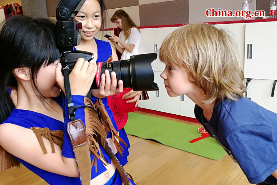 International children have fun with the photographer's professional camera on May 30 during a rehearsal for a performance scheduled on the next day as part of the celebration activities for the International Children's Day. [Photo by Chen Boyuan / China.org.cn]
