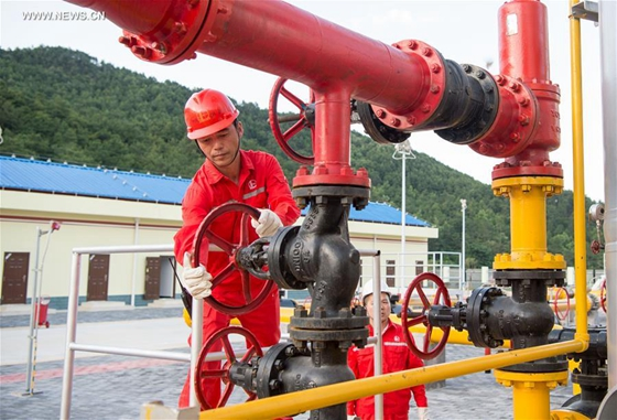Two workers inspect equipments at a newly-operated dehydration station of Fuling shale gas project in Southwest China's Chongqing municipality, May 24, 2016.[Photo/Xinhua]