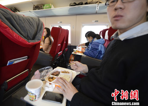 Passengers eat food on the train. China's high-speed railway now offers food which can be booked in advance online. [Photo/Chinanews.com]