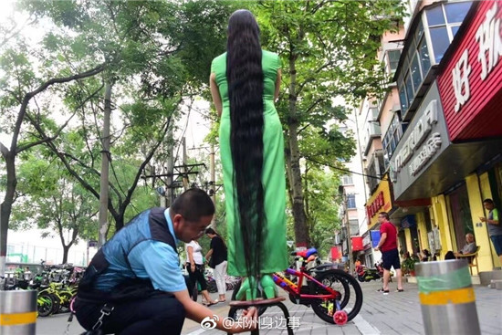 Fan Lili stands on a stool showing that her hair exceeds her height, Zhengzhou, Henan province, on July 30, 2017.